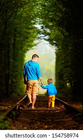 father and son together in railway green tunnel