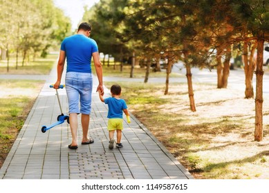 Father and son together walking in the park in a sunny day in shorts. Father is holding hand of his child and carrying a kick scooter. View from back
