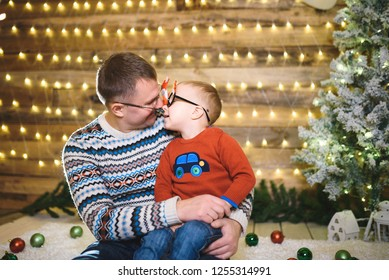 father and son touching noses and smiling in christmas house