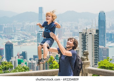 Father and son travelers at the peak of Victoria against the backdrop of Hong Kong. Traveling with children concept.