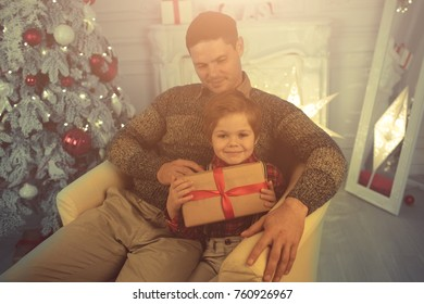 Father and son unwrapping presents on Christmas evening