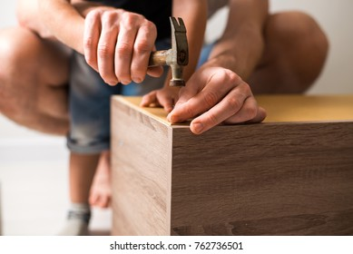 Father and son using hammer and nail spike. Boy helping his dad with building work at home. Family concept
