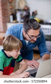 Father and son using laptop in kitchen at home