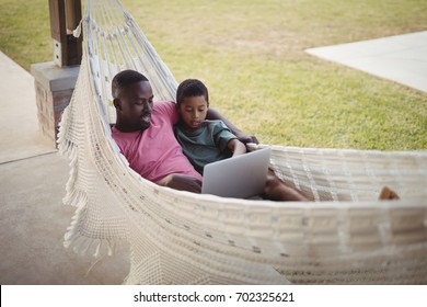 Father and son using laptop while relaxing on a hammock in garden
