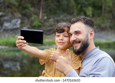Father and son are using smartphone for taking pictures of themselves in forest near river, eco-tourism.