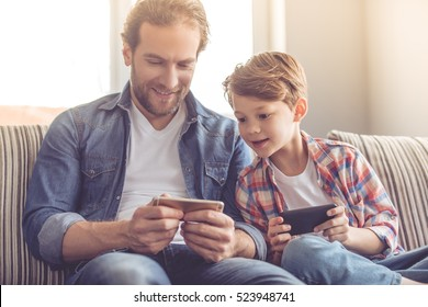 Father and son are using smartphones and smiling while spending time together at home