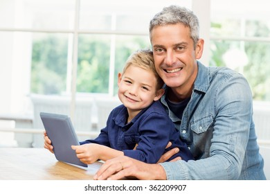 Father and son using tablet at home