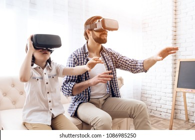 Father and son, using virtual reality glasses, play an interactive game. Future Technology Concept.