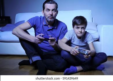 Father and son are very ambitious playing video games at home trying to win