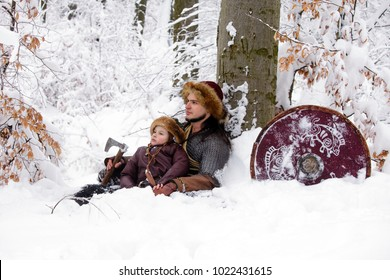 Father and son Vikings in a deep winter forest and the father teaches his son to be a real Viking. Scandinavian traditional clothing for lumberjack, viking concept.