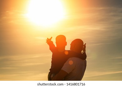father and son walk along the beach at sunset, summer vacation family.