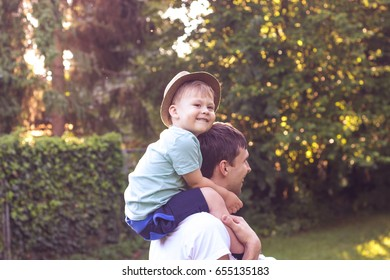 Father and son walk at sunset. Happy dad and young son in the Sun.