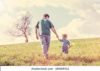 Father and son walking hand in hand up a hill in the spring