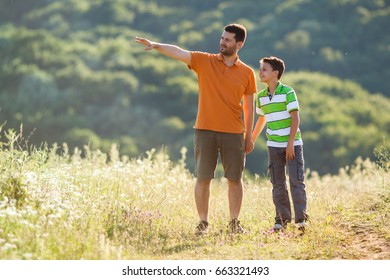 Father and son are walking in nature in summer.