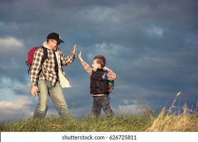 Father and son walking on the field at the day time. People having fun outdoors. Concept of friendly family.