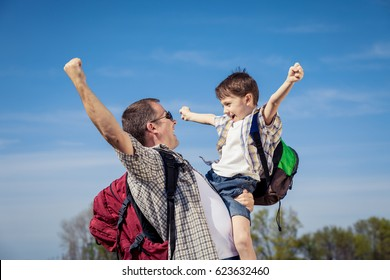 Father and son walking on the road at the day time. People having fun outdoors. Concept of friendly family.