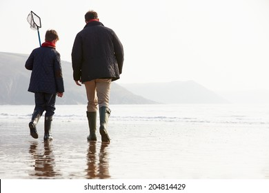 Father And Son Walking On Winter Beach With Fishing Net
