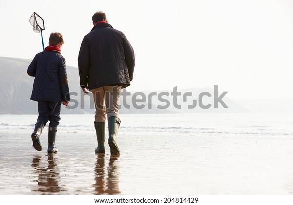 Père Et Fils Marchant Sur La Plage D'Hiver Avec Filet De Pêche