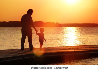 Father and son walking out on a dock at sunset