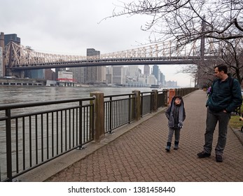 Father and son walking at Roosevelt Island, New York City, winter day.
