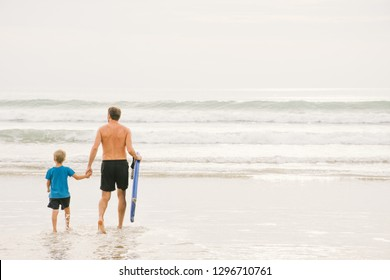 Father and son walking to shallow sea water with boogie board on summer ocean beach. Dad and son get ready to boogie board at the beach. Dad and son having fun on summer vacation in Thailand.