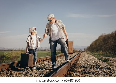 Father and son walking with suitcases on the railway at the day time. People having fun outdoors. Concept of friendly family.