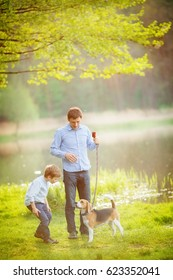 Father and son walking their dog in the park by the lake on a wa