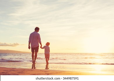 Father and Son Walking Together on the Beach at Sunset. Fatherhood Family Concept