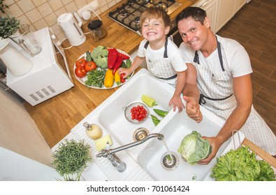 Father with son washes vegetables before eating