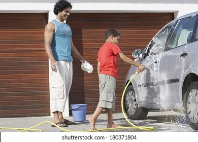Father and son washing the car at home garage