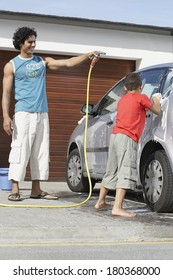 Father and son washing the car near home garage