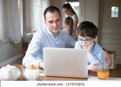 Father and son watching children cartoon online at laptop, dad spending time together with boy teaching him to use computer, curious kid playing game with daddy enjoying morning at home