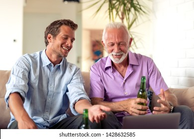 Father and son watching football game on laptop and drinking beer together.