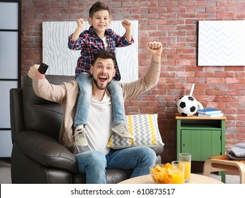 Father and son watching football on TV at home