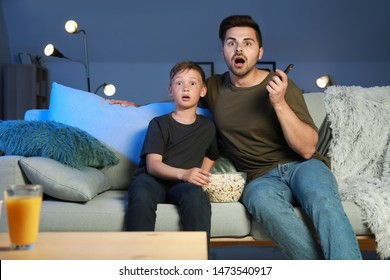 Father with son watching scary movie in evening