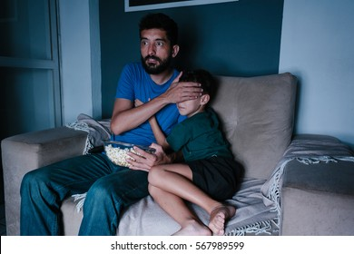Father and son watching scary movie on tv at night. Father covering his son's eyes