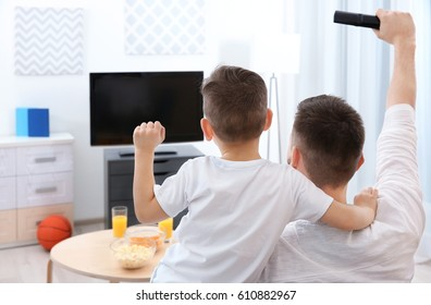Father and son watching sports on TV at home