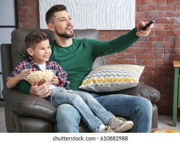 Father and son watching TV at home
