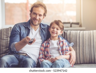 Father and son are watching TV and smiling while spending time together at home