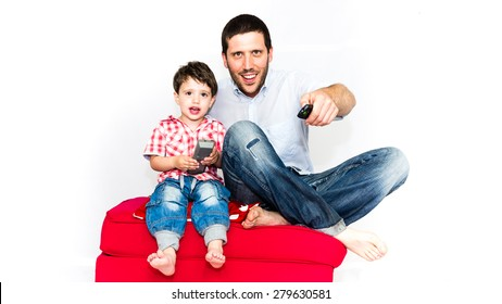 Father and son watching tv together on a red sofa - isolated on white background