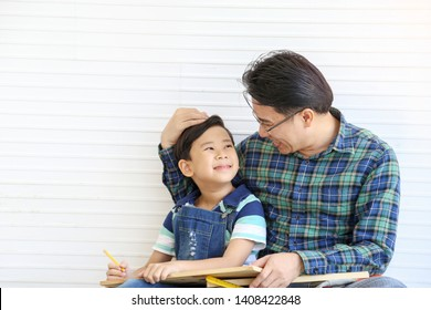 Father and son wearing casual chess blue shirt was smiling together with happiness, happy family relationship concept.