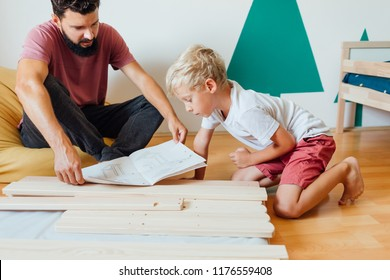 Father And Son Working On Carpentry At Home Using Blueprint