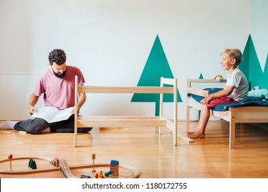 Father And Son Working On Carpentry At Home in Kid's Room Using Blueprint