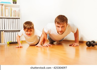 Father and son working up, doing pushups at home