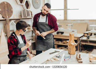 Father and son in workshop tinkering wooden toy. Dad teaching little son to repair. Fatherhood and sharing of experience concept. Teacher with male kid working with tool, using screwdriver