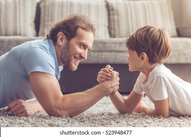 Father and son are wrestling and smiling while spending time together at home