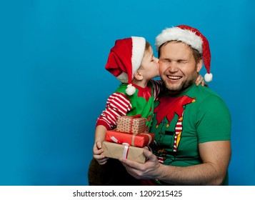 Father and son with xmas gifts. Portrait of stylish child and man in Santa red hats looking for Christmas gifts. Funny family isolated on blue. Son and dad with stack of magic boxes. Child kiss father