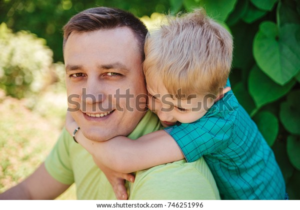 Father and son.Little boy is embracing father's shoulders.Family cute moments.
