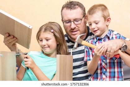 Vater und Söhne bauen die Möbel zu Hause