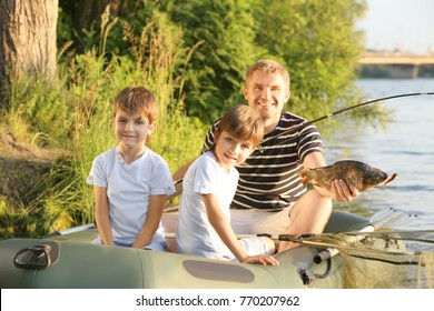 Father with sons fishing from boat on river